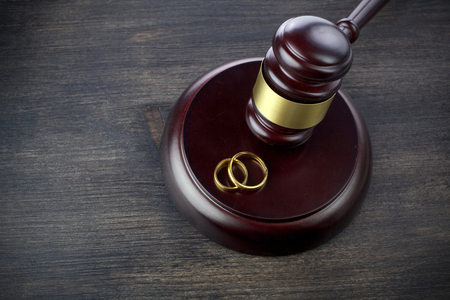 Wedding rings hammer of a judge on a dark wooden background. Divorce proceedings Stock fotó