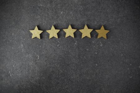 five golden stars on dark background, top rating concept 免版税图像