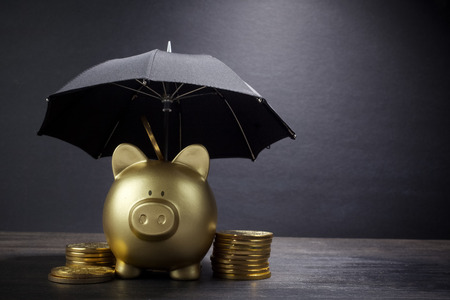 Gouden spaarvarken met overkoepelend concept voor financiële verzekering, bescherming, veilige investering of bankieren Stockfoto
