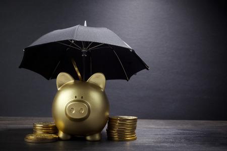 Hucha de oro con concepto de paraguas para seguros financieros, protección, inversión segura o banca Foto de archivo