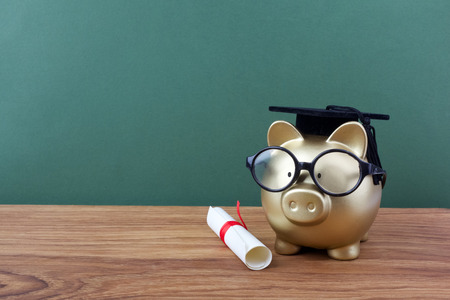 Gfold piggy bank with a grad cap and diploma in front of green chalkboard. Education scholarship Stock Photo