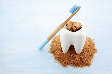 Ceramic tooth in big pile of brown sugar. Caries and sugar concept. Dental care concept