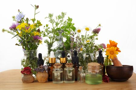 Essential oils with herbs and flowers on wooden table Stock Photo