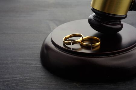Two broken rings and hammer of a judge. Divorce concept
