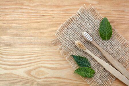 Concepto de desperdicio cero. Cepillo de dientes de bambú sobre fondo de madera con hojas de menta verde. Lo esencial sin plástico, cuidado de los dientes.