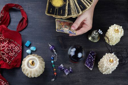 Fortune teller female hands and tarot cards on dark wooden table. Divination concept. Stock Photo - 127511652