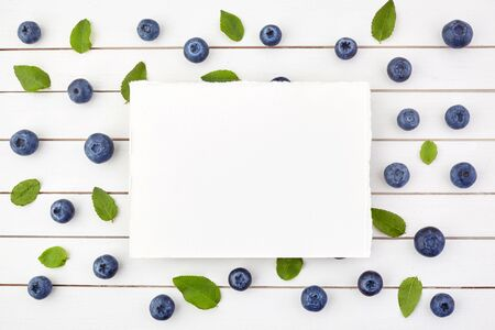 Framework made of blueberry on white wooden background. Flat lay. Food concept. Banco de Imagens