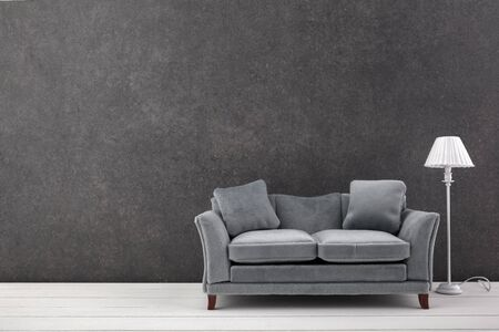 Modern grey sofa on grey wall background. Free space