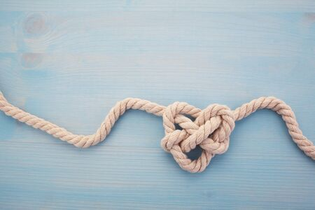 Heart shaped knot on blue wooden background