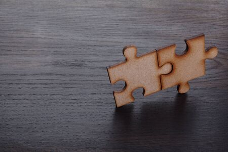 Two Wooden pieces of jigsaw puzzle on wooden background