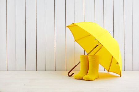 A pair of yellow rain boots and a umbrella on white wooden background Stock fotó