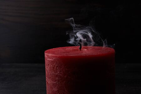 Red extinguished candle with smoke trailing off the wick on black background