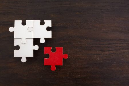 Three onnected jigsaw puzzle pieces and one red on dark wooden background. Finding the right solutions in teamwork. 写真素材