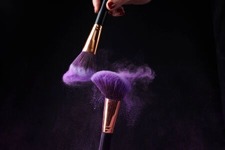 Make-up brushes with silver powder explosion on black background