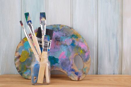 Wooden art palette with paints and brushes on colored wooden background Archivio Fotografico - 131137390