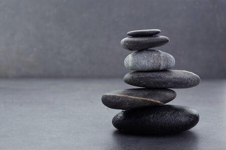 zen stones in balanced pile on dark grey background