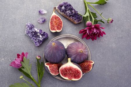 A few fresh figs in a bowl on an old dark background.