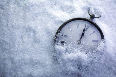 Reloj de tiempo de Navidad bajo la nieve blanca, cuenta regresiva para la medianoche