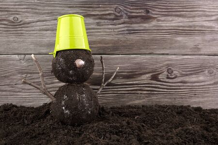 Snowman with a green pot made from soil without snow. Фото со стока