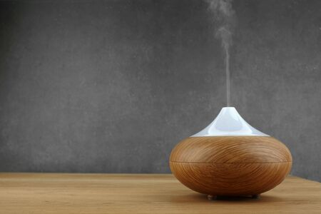 Aroma oil diffuser on wooden table and grey background