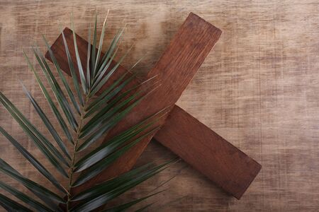 Palm Sunday. Palm brunch on wooden background with cross. Easter