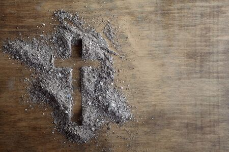 Christian cross symbol made of ash on a wooden background