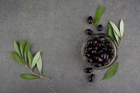 Black olives in glass bowl. Top view on dark background. Stok Fotoğraf