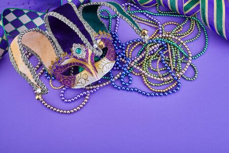 Colorful Mardi Gras mask on purple background with beads and ribbons. Top view. Copy space