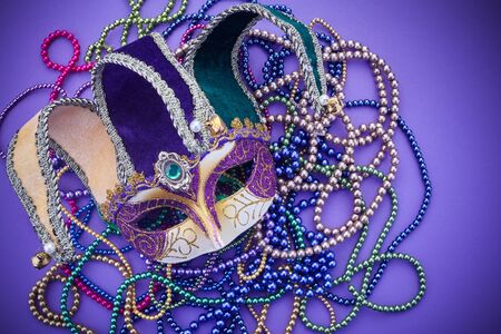 Festive mardi gras, venetian or carnivale mask on a purple background. Top view Stock Photo