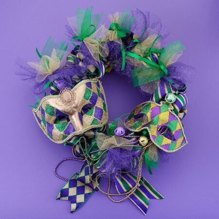 Mardi gras wreath on purple background with Mardi gras mask