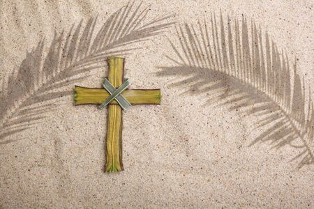 Palm Sunday. Cross and palm shadows on sand background