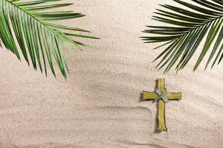 Cross and Palm Tree Leaves on sand. Palm sunday concept. 스톡 콘텐츠