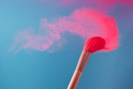 close-up photo of two professional make-up brushes with pink powder in motion on blue background