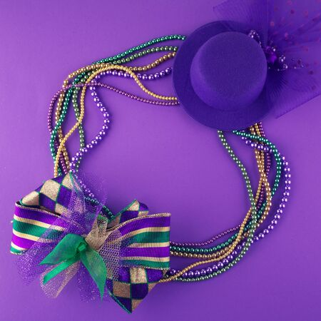 Mardi Gras beads and mask making a frame with copy space on a purple background Stockfoto