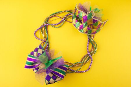 Mardi Gras beads and mask making a frame with copy space on a yellow background