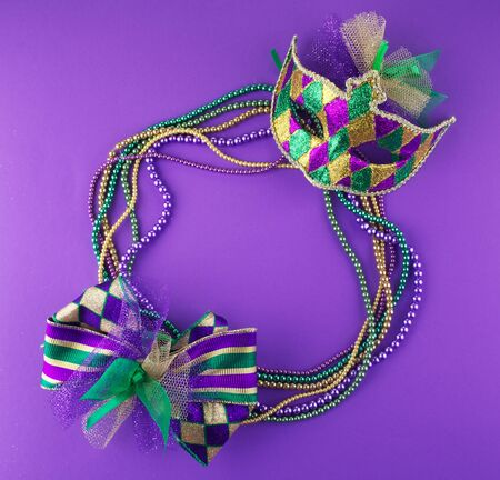 Mardi Gras beads and mask making a frame with copy space on a purple Stockfoto