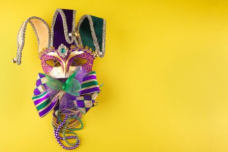 A festive, colorful mardi gras or carnivale mask on a yellow background. Venetian masks.
