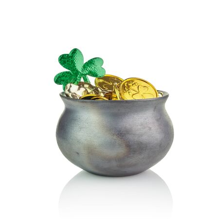 Black pot of leprechauns gold with lucky clovers isolated on white