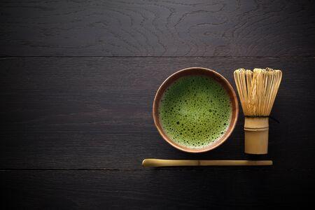 Matcha-Pulver. Organische grüne Matcha-Teezeremonie. Gesundes Getränk. Traditionelles japanisches Getränk auf schwarzem Holzhintergrund