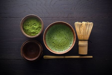 Matcha powder. Organic green matcha tea ceremony. Healthy drink. Traditional japanese drink on black wooden background Banque d'images