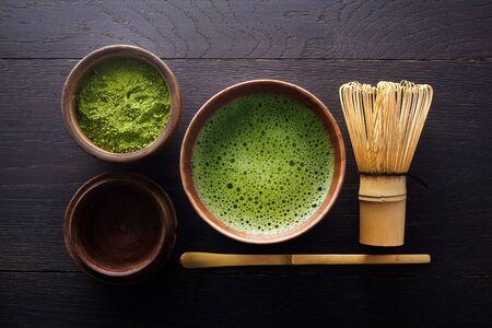 Matcha powder. Organic green matcha tea ceremony. Traditional japanese drink on black wooden background