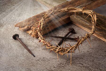 Fondo de Pascua que representa la crucifixión con una cruz de madera rústica, corona de espinas y clavos. Foto de archivo