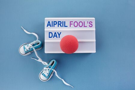 April fools day. Surprise symbol. Shoelaces tied together on blue wooden background. April fool.