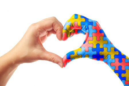 World Autism Awareness day, mental health care concept with puzzle jigsaw pattern on heart shape hands.