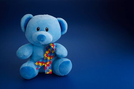 World Autism Awareness, concept with teddy bear holding puzzle or jigsaw pattern ribbon on blue paper background