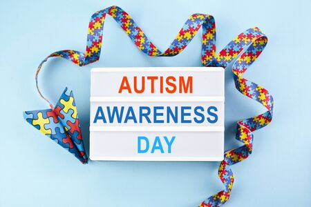 Autism awareness day or month. Paper plane in origami style with autism awareness puzzle ribbon on blue background.