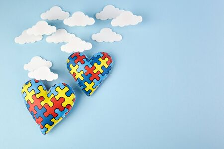 World autism awareness day. Awareness healthcare concept. Puzzle hearts on blue background