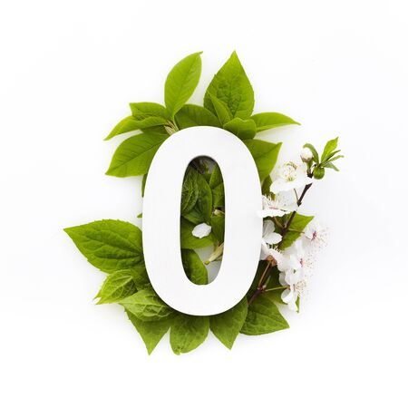 Number zero with green leaves. Minimal summer concept. Flat lay.