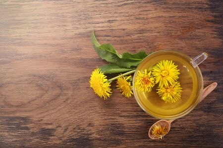 Cup ph healthy dandelion tea on vintage wooden background. Fresh herbs