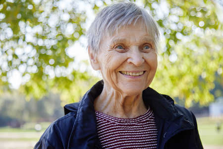 Portrait of ninety year old woman is smiling in the park.